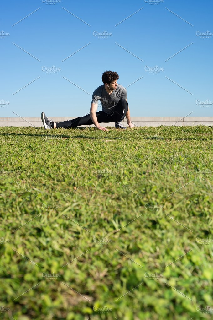 man stretches the leg in the ground space for text down.jpg - Sports