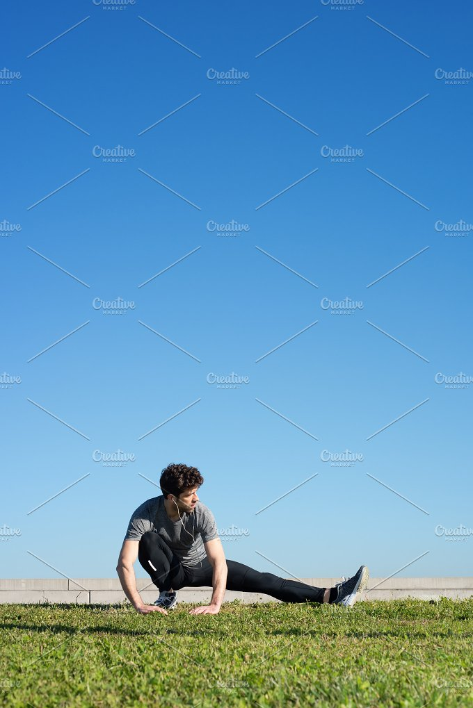 man stretches the leg in the ground space for text up.jpg - Sports