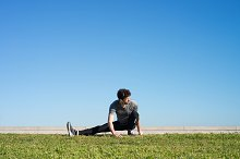 man stretches the leg in the ground space for text.jpg