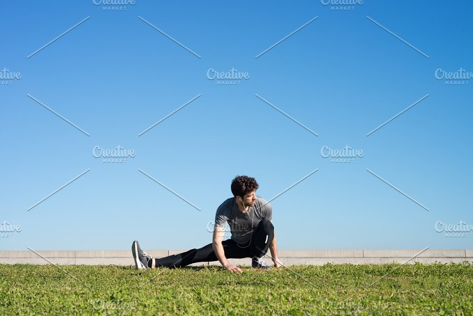 man stretches the leg in the ground space for text.jpg - Sports
