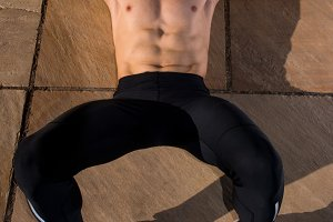 Man without t-shirt makes abdominal in the ground.jpg