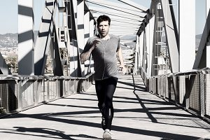 young man running with earpieces by metal bridge.jpg
