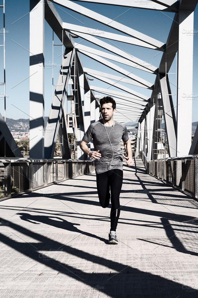 young man running by metal bridge.jpg - Sports