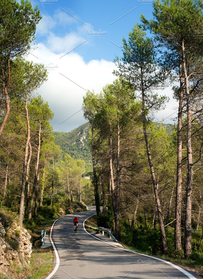 Cyclist in road with curves and mountain.jpg - Sports