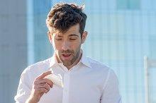Man with handkerchief sneezes.jpg