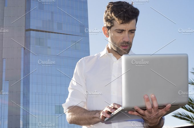 Man with laptop outdoors.jpg - Business