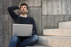 worried or alleviated young man with laptop space for text.jpg