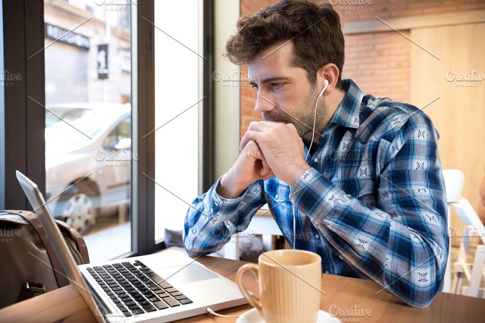 Young man listens to and watches orenador with cup you or coffee.jpg - Technology