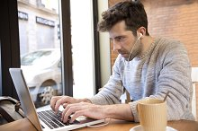 Young man listens to and write on computer with cup of coffee.jpg