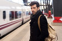 Young man waits for train in station