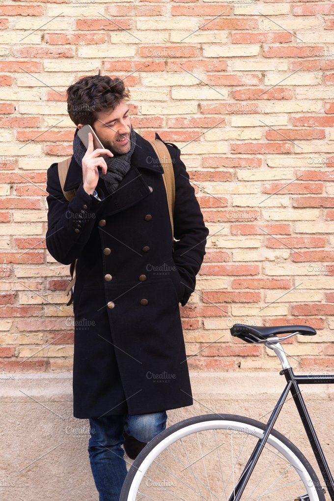 young man with bicycle and shelter speaking on the telephone.jpg - Technology