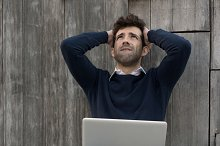young man with laptop worried with the hands in the head.jpg