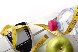 Scale with bottle, apple and tape