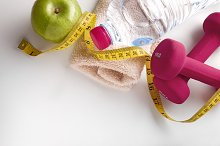 Pink dumbbells with apple and tape