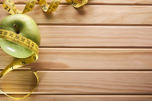 Apple and tape measure on wooden floor top view.jpg