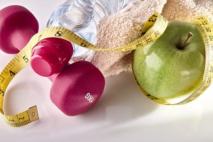 Apple dumbbells and tape measure on white table elevated top.jpg
