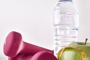 Apple dumbbells tape and bottle on white table front isolated.jpg