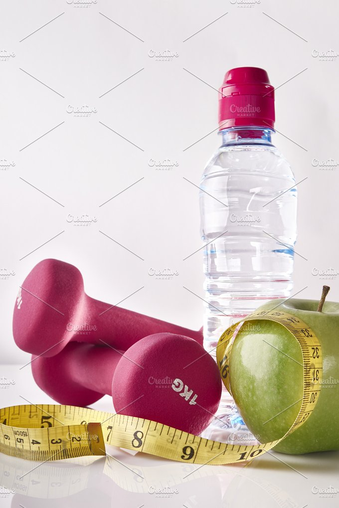 Apple dumbbells tape and bottle on white table front isolated.jpg - Health