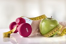 Apple dumbbells and tape measure on white table front gym.jpg