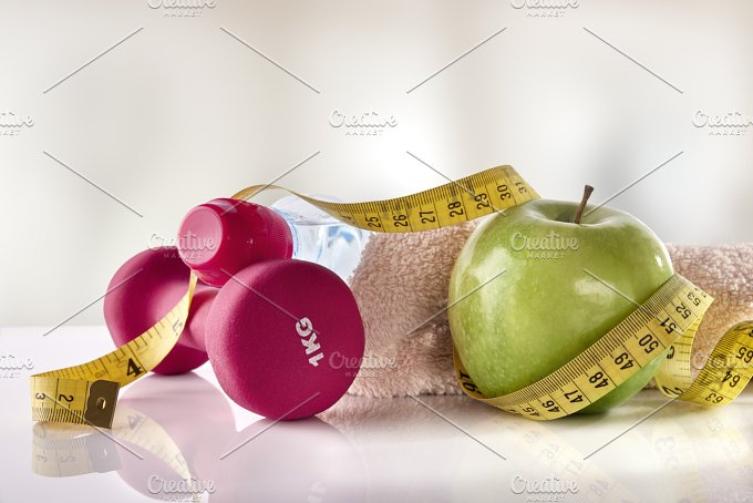 Apple dumbbells and tape measure on white table front gym.jpg - Health