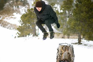 Young man jumping into snow