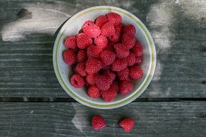 Raspberries in the bowl on wooden ta