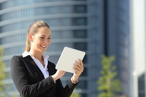 Business woman using a tablet in the street.jpg