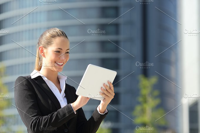 Business woman using a tablet in the street.jpg - Business