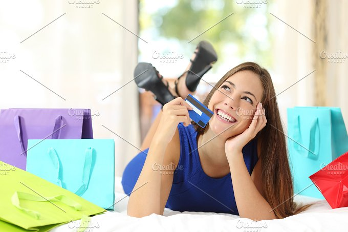 Girl with a credit card thinking what to buy at home.jpg - Business