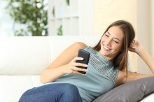 Happy housewife using a mobile phone on a couch.jpg
