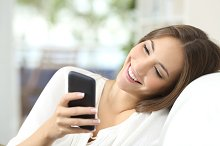 Girl texting on a mobile phone at home.jpg