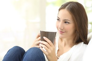 Pensive girl holding a coffee cup at home.jpg