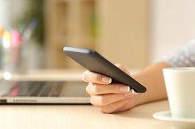 Woman hand using a smart phone on a desk.jpg
