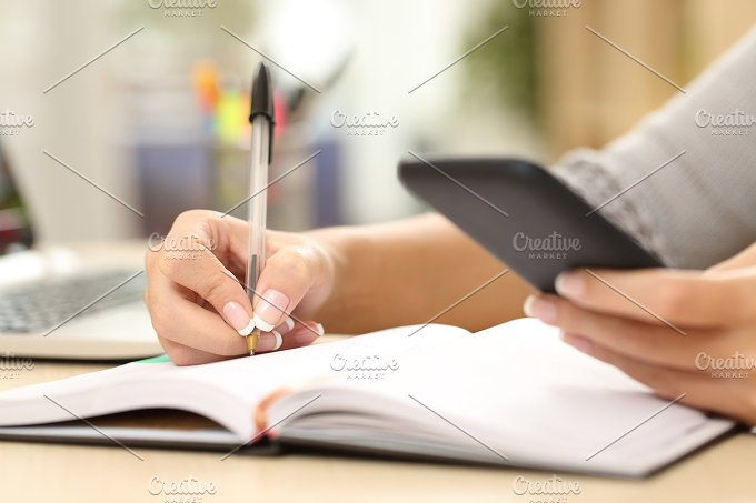 Woman hand writing in agenda consulting phone.jpg - Technology