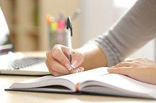 Woman hand writing in an agenda at home.jpg