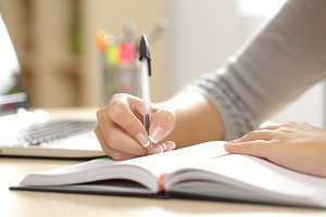 Woman hand writing in an agenda at home.jpg