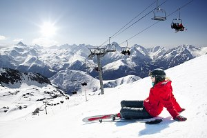 Girl skier lying on snow with ski