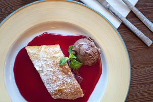 Plate with cherry strudel and syrup