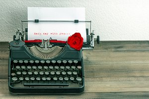 Vintage typewriter with red rose