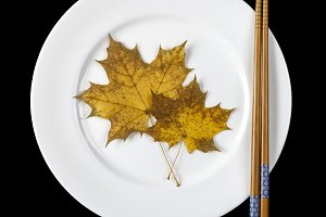 Plate, chopsticks and maple leaves