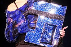 Woman cares blue shiny handbag