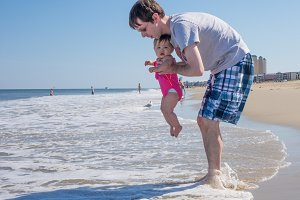 Young baby girl in ocean with dad