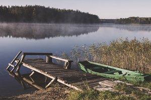 Foggy lake with bridge and boat
