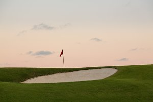 Golf green and flag as sun sets