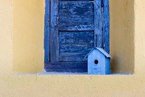 Wooden bird house in window