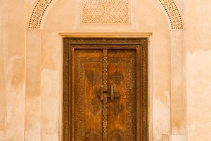 Ornate carved wooden door in wall