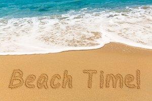 Sand writing Beach Time by ocean