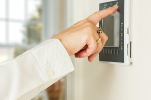 Woman's hand pushes thermostat