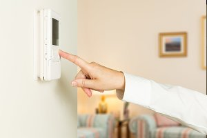 Female hand pushes thermostat