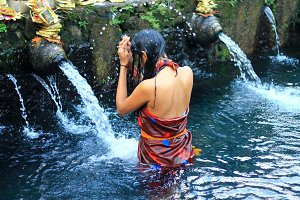Balinese girl praying in the water